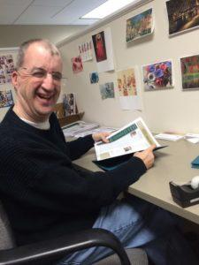 smiling man holding brochure
