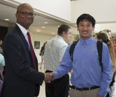 what appears to be a man in a suit shaking hands with a man blue project SEARCH shirt