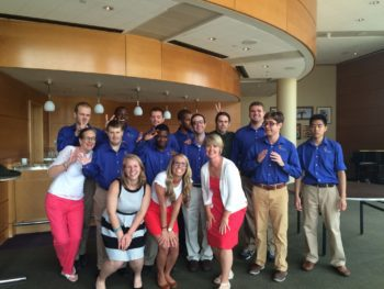 Large group of people standing in a lobby, some are wearing blue project search shirts and some of them are wearing red and white.