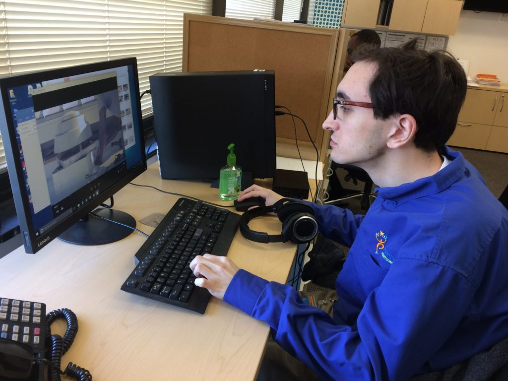A person sitting at a desk focused on computer and working.